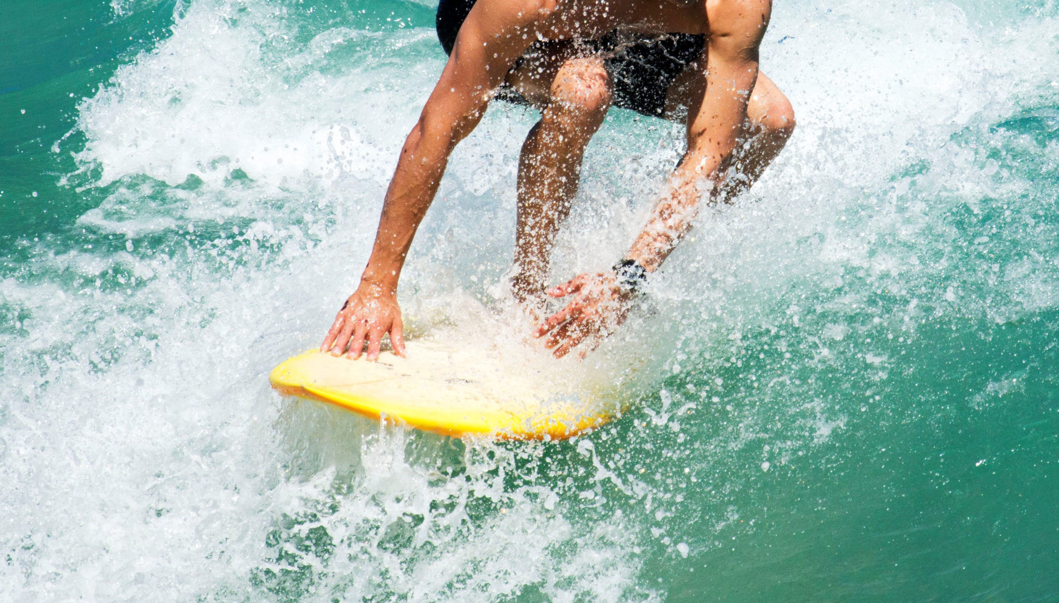 A man staying low on his board while surfing